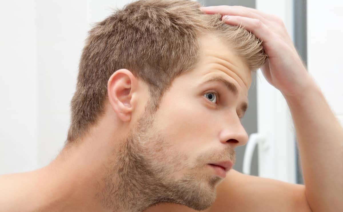 Handsome unshaven man looking at his receding hairline in the mirror.