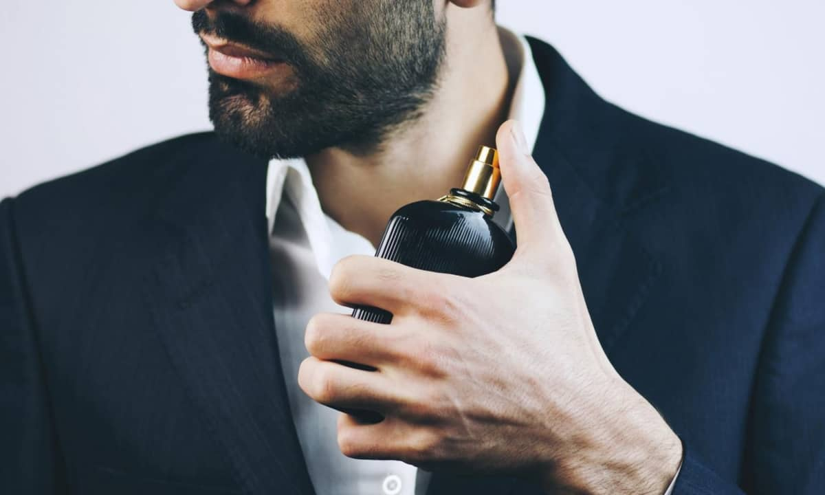 Handsome man spraying fragrance