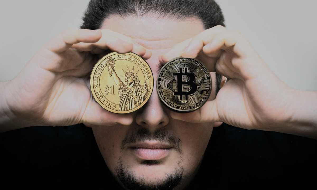 man holding coin currency to eyes