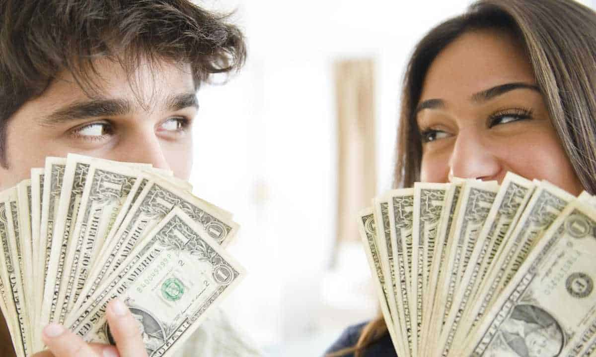 Couple holding cash money to their face.