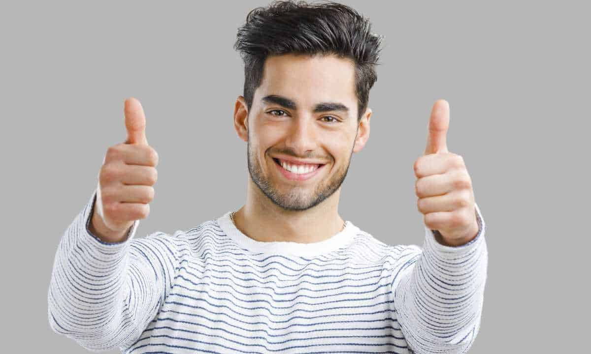 Portrait of handsome and confident man giving two thumbs up.